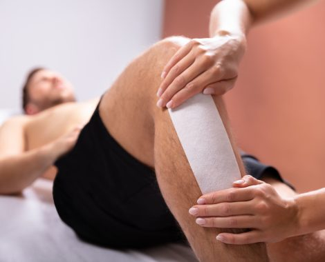 Close-up Of Therapist Hand Waxing Man's Leg With Wax Strip